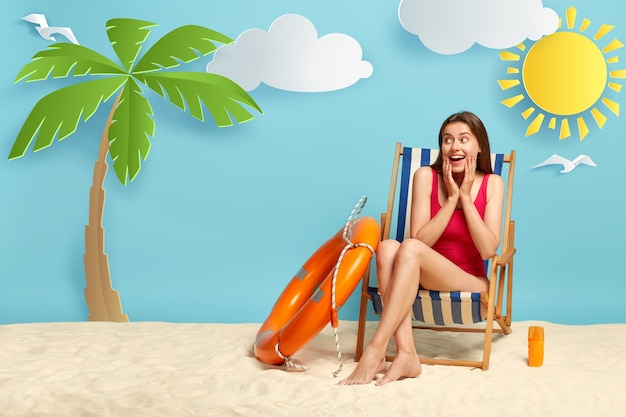 Happy surprised female model in red swimsuit, poses on deck chair at tropical beach with white sand, palm