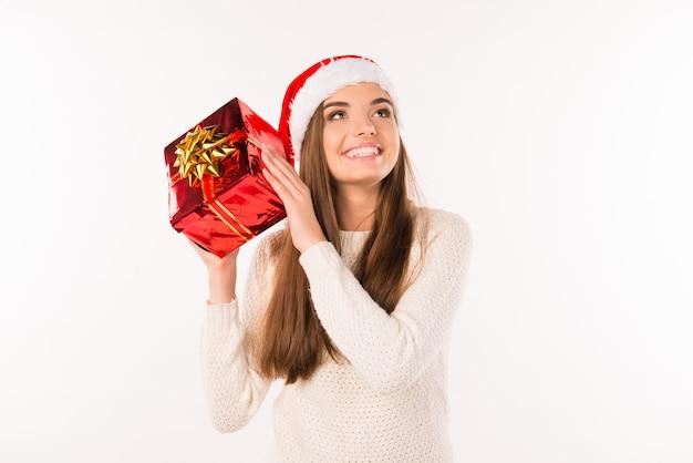 Счастливая удивленная девушка в новогодней шапке с рождественскими подарками