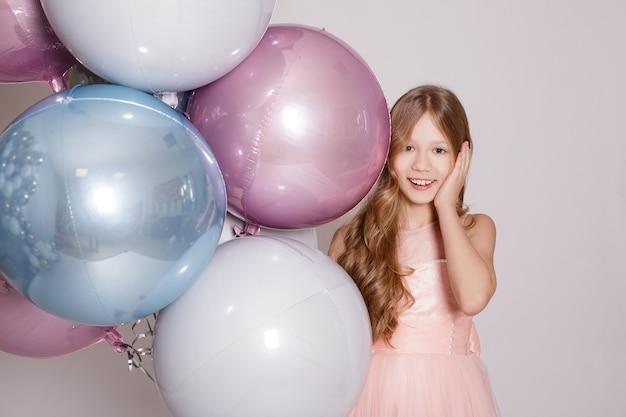 白い背景の上のスタジオでパステル気球と幸せな驚きの女の子