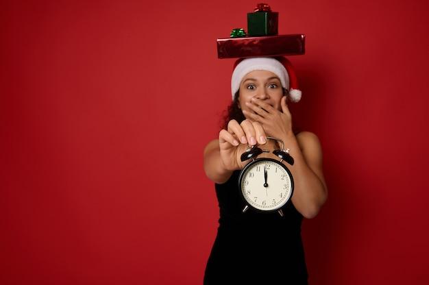 검은 드레스와 산타 모자를 쓰고 머리에 선물 상자를 얹은 행복한 놀란 아름다운 여성은 카메라를 바라보며 밤 12시경 알람 시계를 보여주는 입을 가리고 있습니다. 크리스마스 컨셉