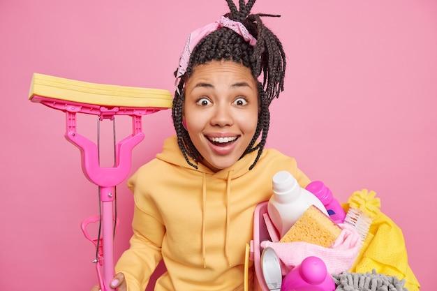 Счастливая удивленная домохозяйка пытается поддерживать чистоту в доме, принимает сложные задания с корзиной для белья и шваброй