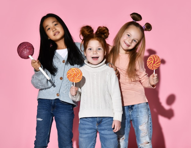 Happy surprised kids screaming and laughing while posing with huge lollipop and spiral sweet candies, studio portrait isolated on pink background. funny crazy facial expression and sugar addiction