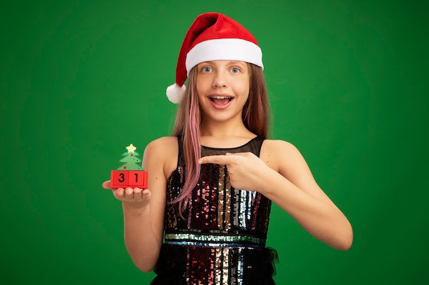 Happy and surprised little girl in glitter party dress and santa hat showing toy cubes with new year date pointing with index finger at it smiling cheerfully standing over green background