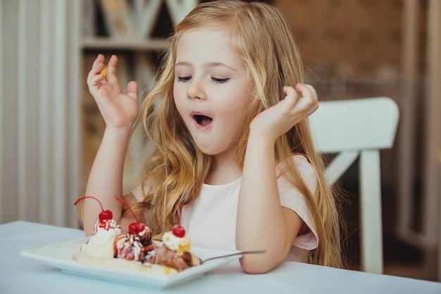 Счастливая удивленная маленькая девочка, подающая мороженое с фруктами в кофе.