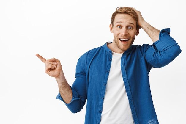Felice uomo sorpreso sorridente, puntando il dito a sinistra e toccando la testa stupito, non posso credere alla sua fortuna, ha trovato qualcosa di interessante, in piedi sul muro bianco