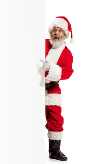 Happy surprised santa claus pointing on blank advertisement banner background with copy space. smiling senior man showing at white blank of empty poster