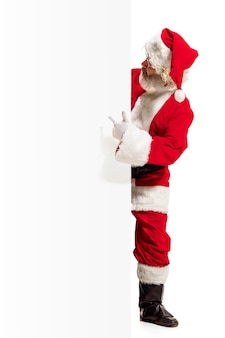 Happy surprised santa claus pointing on blank