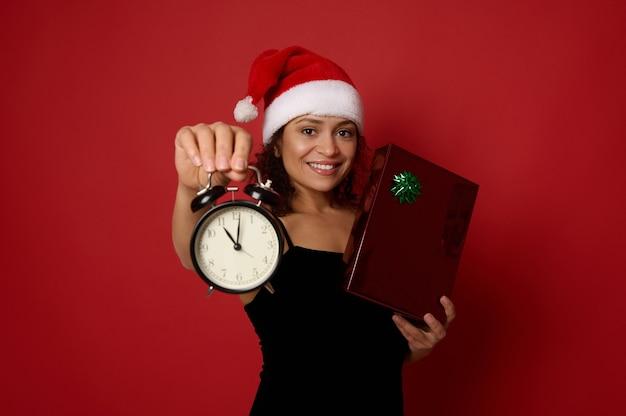 검은 이브닝 드레스와 산타 모자를 쓴 행복한 웃고 있는 여성이 크리스마스 선물 상자를 들고 밤 12시경 알람 시계를 보여주며 카메라를 보고 있습니다. 크리스마스 컨셉