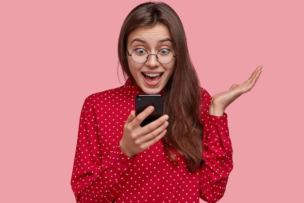 幸せな驚きの社交的な女性は、携帯電話の画面を積極的に見て、良いニュースを受け取り、オンライン通信に最新の技術を使用しています