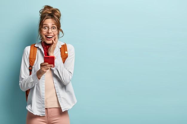 Счастливый удивленный подросток выглядит радостно, держит красный сотовый телефон, получает сообщение о доходах
