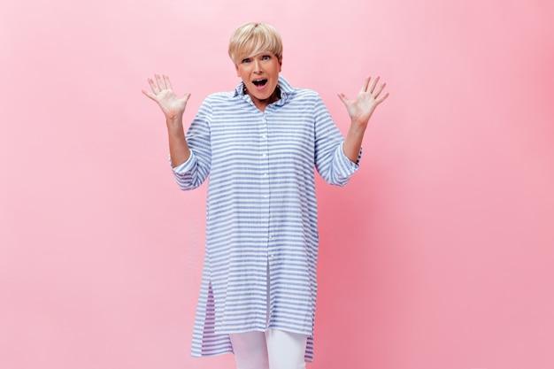 Счастливая удивленная женщина в клетчатом наряде позирует на розовом фоне