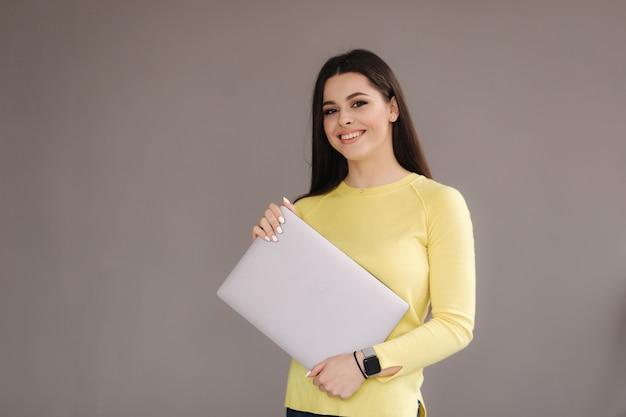 Счастливый удивлен женщина в желтой толстовке держит ноутбук и подняла руку к лицу.