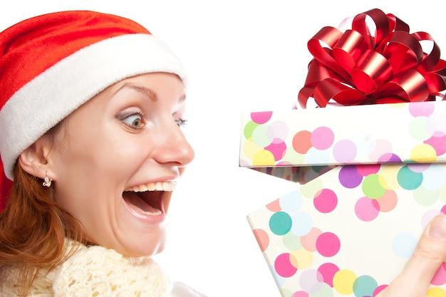 Счастливая удивленная женщина открывает рождественский подарок
