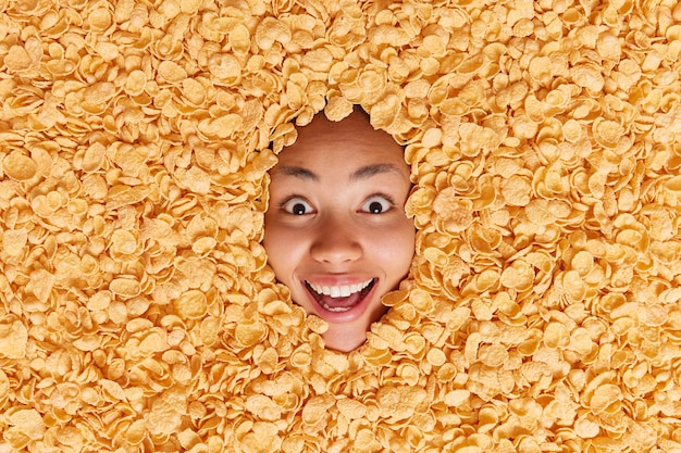 Happy surprised woman stares has broad smile cannot believe her eyes buried in dry cornflakes lies around cereals reacts on something exciting going to have breakfast