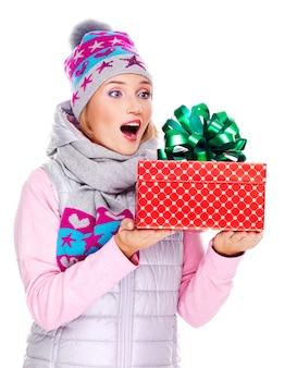 Счастливая удивленная женщина с рождественским подарком в зимней верхней одежде изолирована на белом