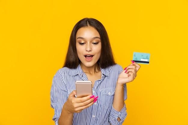Счастливая удивленная женщина с телефоном и кредитной картой. концепция покупок в интернете.