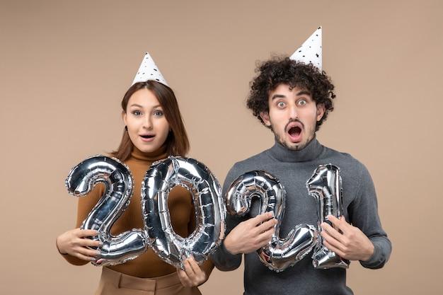 Счастливая удивленная молодая пара в новогодней шапке позирует для камеры девушка показывает и парень с серым и на сером
