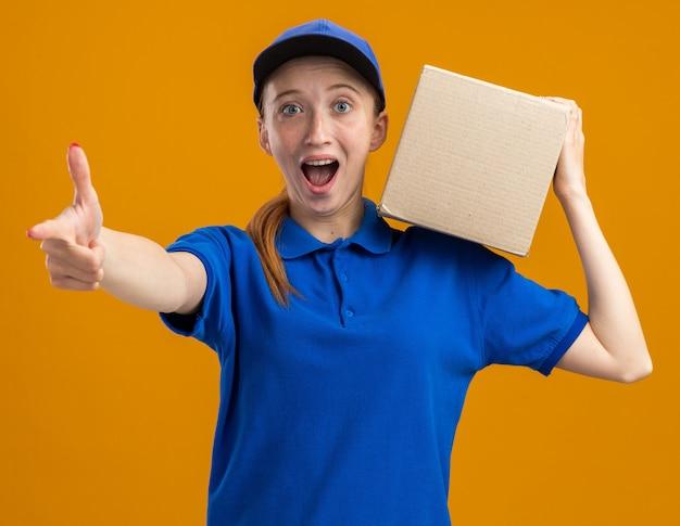 Felice e sorpresa giovane ragazza delle consegne in uniforme blu e berretto che tiene in mano una scatola di cartone sorridente fiduciosa che mostra i pollici in su in piedi sul muro arancione