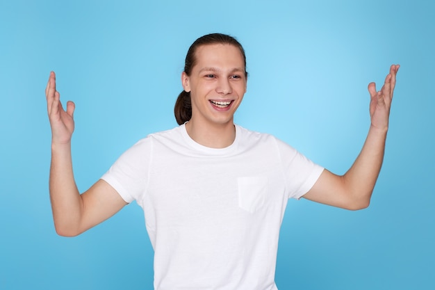 青い背景で隔離のtシャツで幸せな驚きの若いハンサムな男。人間の感情、顔の表情