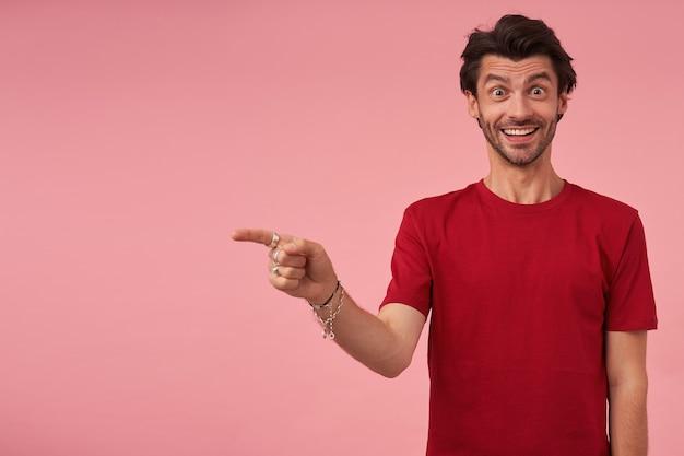 立って横を指している赤いtシャツの剛毛で幸せな驚きの若い男