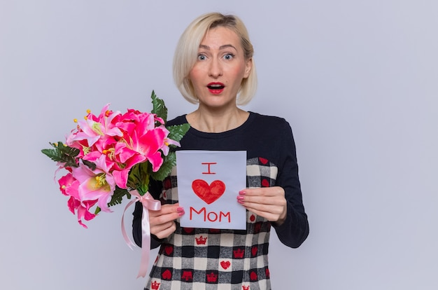 Happy and surprised young woman in beautiful dress holding greeting card and bouquet of flowers looking at front celebrating mother's day standing over white wall