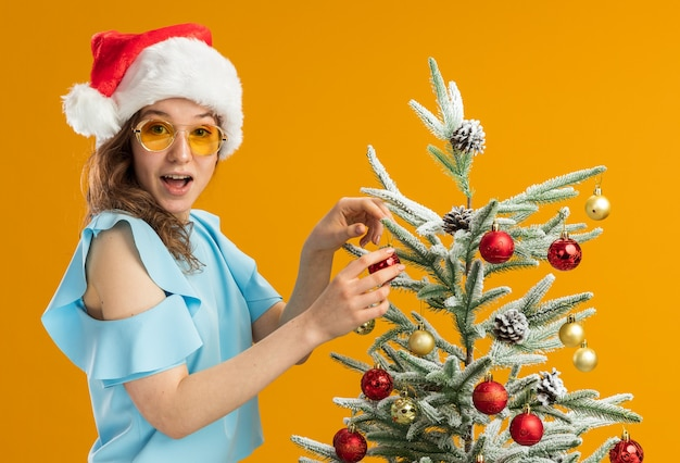 Happy and surprised young woman in blue top and santa hat wearing yellow glasses decorating christmas tree standing over orange background
