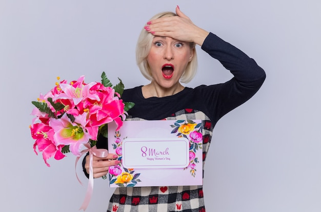 Happy and surprised young woman holding greeting card and bouquet of flowers