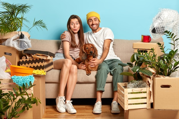 Happy surprised young woman and man embrace while sit on sofa