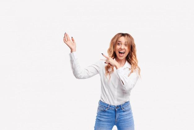 Счастливый удивлен молодая женщина, широко улыбаясь в камеру, указывая пальцами вверх, показывая что-то интересное и захватывающее на белом