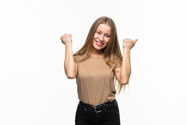 Счастливая удивленная молодая женщина с поднятыми кулаками празднует победу изолированно на белой поверхности