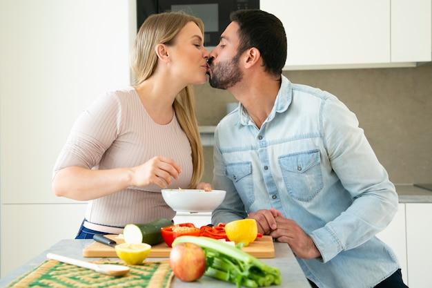 幸せな甘い若いカップルが一緒に夕食を調理しながらキス、キッチンでまな板で新鮮な野菜をカット、笑顔で話しています。愛と料理のコンセプト