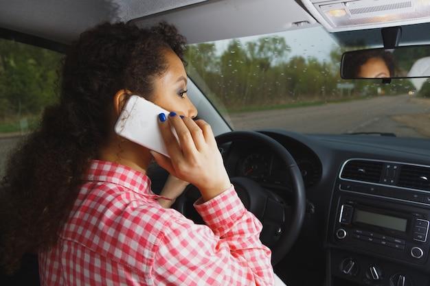 顧客に携帯電話を見せる幸せなタクシー運転手