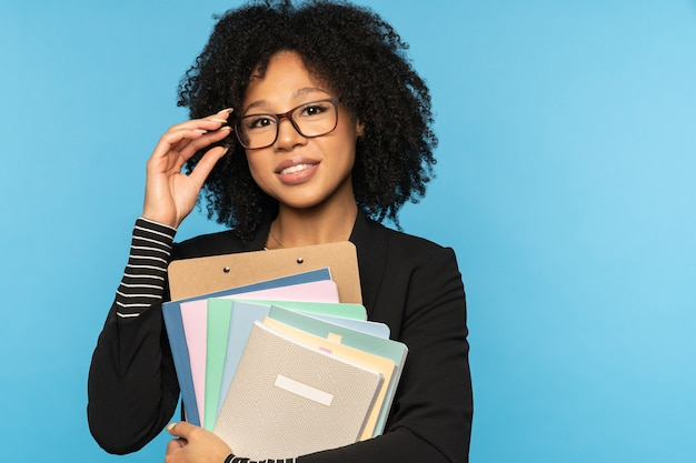 Happy teacher holding notebooks documents and folder isolated on blue