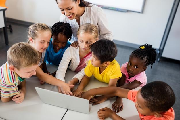 Happy teacher and pupils using laptop