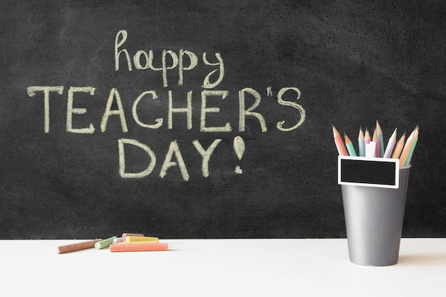 Happy teacher's day on blackboard and pencils