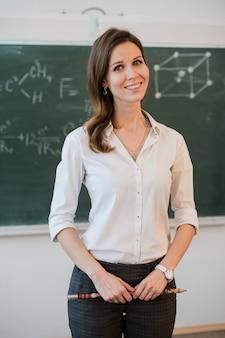 Счастливый учитель стоит перед черной доской