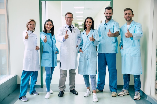 Счастливая команда успешных и уверенных в себе современных врачей позирует и смотрит в камеру в коридоре больницы