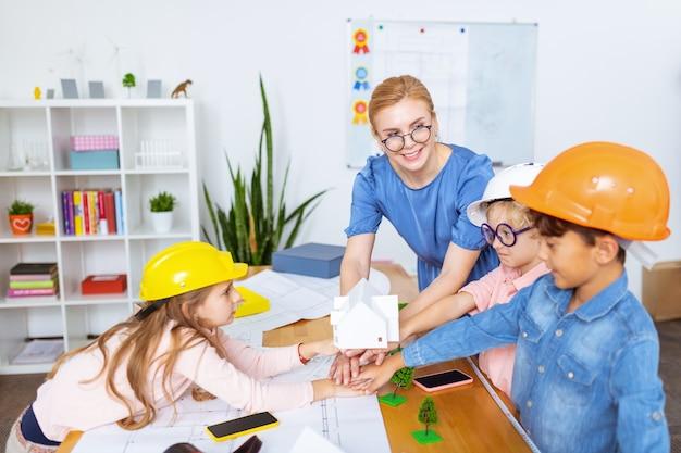 Счастливая команда. ученики и учитель счастливы после моделирования умного города и рисования эскизов