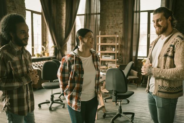 Счастливая команда разговаривает, стоя в коворкинг-пространстве