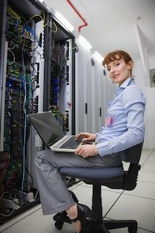 Счастливый техник, сидя на поворотном стуле, используя ноутбук, чтобы диагностировать серверы