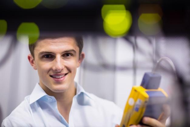 Счастливый техник, использующий цифровой анализатор кабеля на сервере