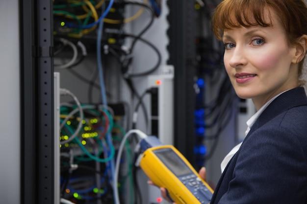 Happy technician using digital cable analyzer on server