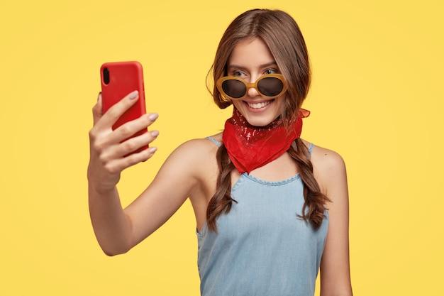 Felice teeanage ragazza in abito elegante e occhiali da sole, tiene il cellulare rosso davanti, fa il ritratto di selfie, sorride delicatamente, posa contro il muro giallo. concetto di gioventù, tecnologia e passatempo