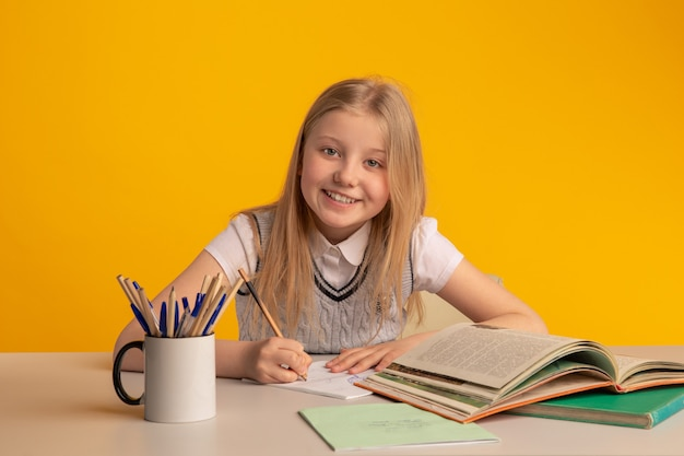 Счастливая девушка подросткового возраста улыбается и изучает что-то в желтом классе.