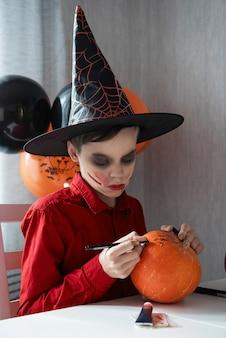 カボチャを描くハロウィーンのお祝いの準備をしている衣装を着た幸せな10代の少年