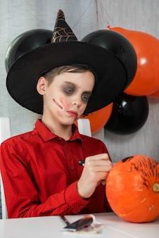 Счастливый мальчик-подросток в костюме готовится к празднованию хэллоуина, рисуя тыкву