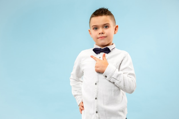 Счастливый подросток мальчик улыбается изолированные на синем фоне студии. красивый мужской поясной портрет. молодой эмоциональный ребенок, указывающий налево. в