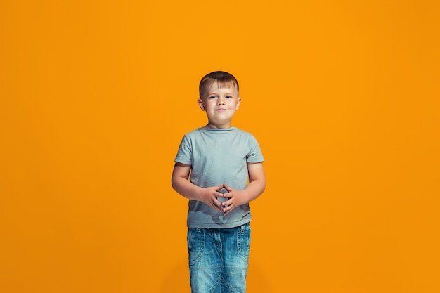 The happy teen boy standing and smiling against orange space.