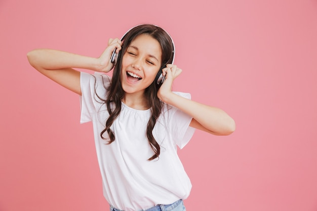 Happy teen girl 8-10 in casual clothing singing with closed eyes while listening to music via wireless headphones, isolated over pink background