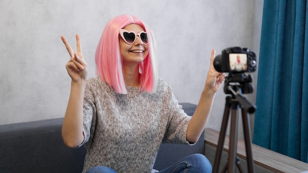 Happy teen girl blogger with smiling face in pink wig and glasses. shows the victory sign, looking at camera recording live vlog